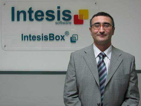 Pere Lumbreras, Director General de Intesis Software delante del logotipo de la empresa.