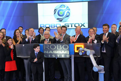 El brazo del robot UR5 de Universal Robots tocando la campana del cierre del Índice NASDAQ