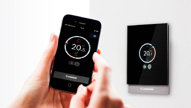 Una mano con un móvil controlando un termostato.
