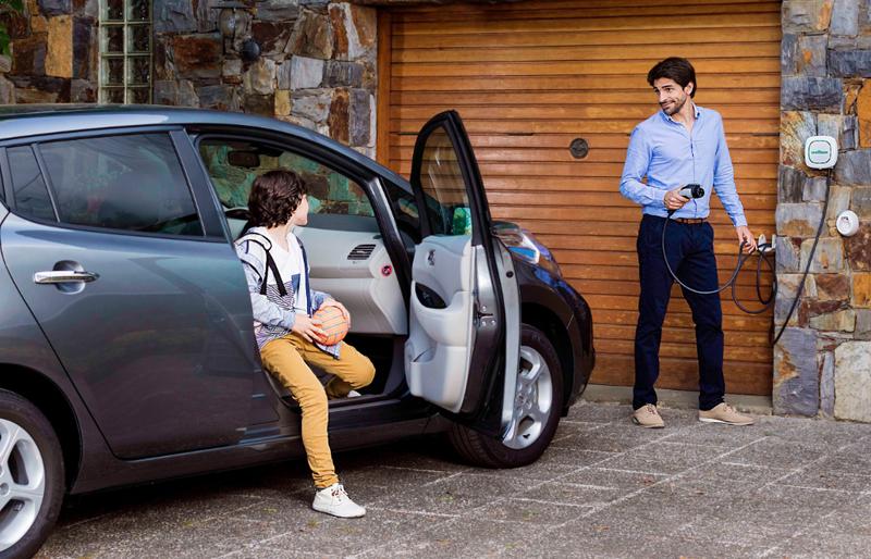 Dos personas cargando un coche electrico.