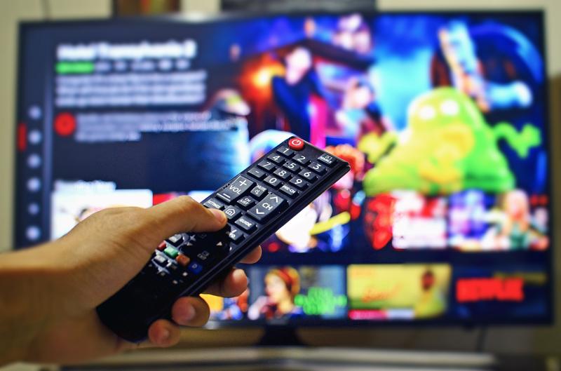 Una mano con un mando a distancia delante de un televisor.