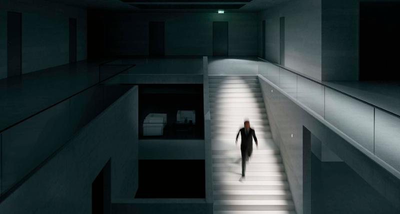 Una persona bajando una escalera iluminada en la oscuridad.