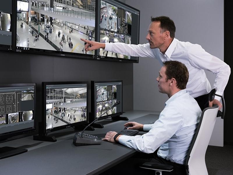 Dos personas de seguridad visionando múltiples cámaras.