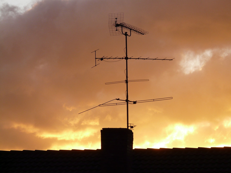 Una antena de televisión encima de una vivienda.