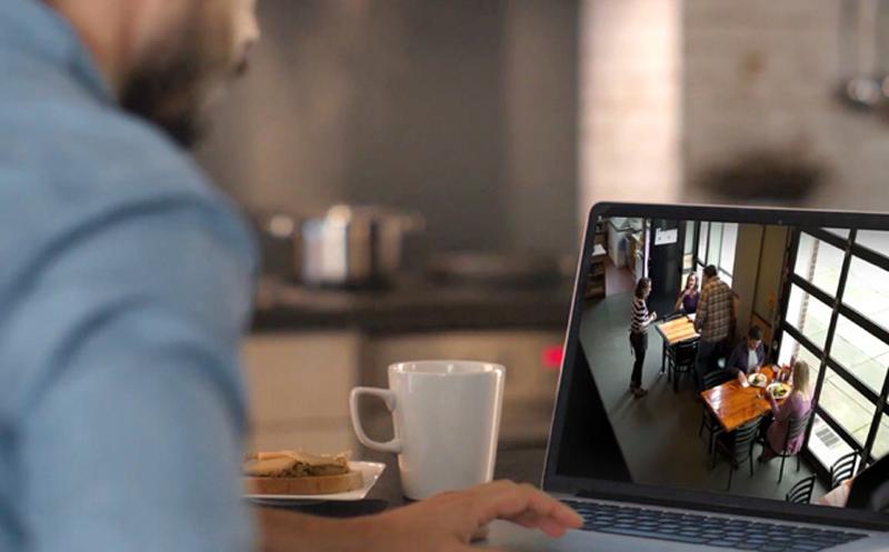 Un hombre sentado en su casa mientras mira un portátil con las imágenes que captura la cámara de seguridad.