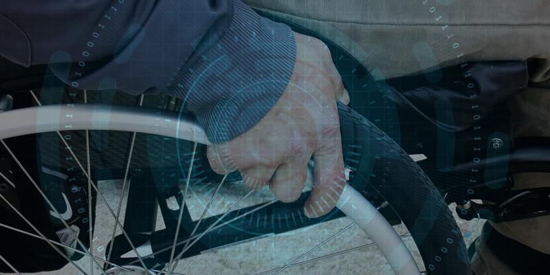 Una mano en la rueda de una silla de ruedas y un fondo de ceros y unos representando las tecnologías digitales.