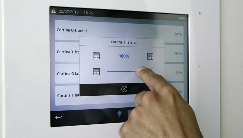 Una mano controlando parámetros de unas persianas en una pantalla táctil.