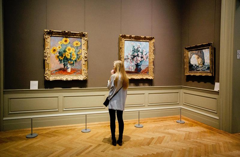 Una chica delante de varios cuadros en el interior de un museo.