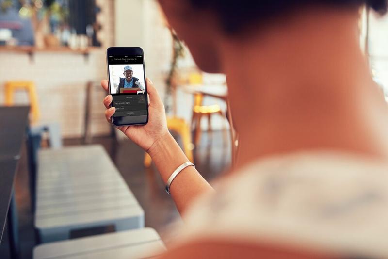 Una mujer con un móvil en la mano recibiendo una llamada de su videoportero.