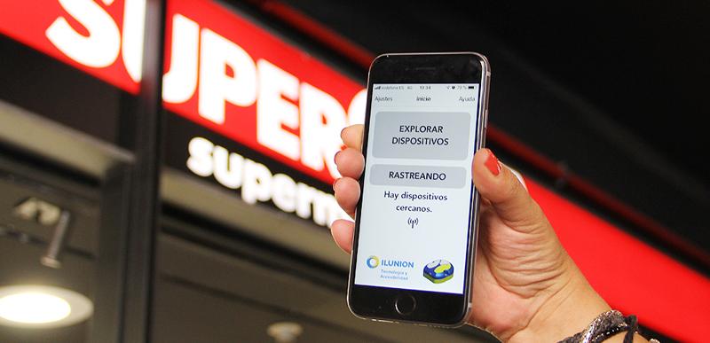 Una mano con un móvil que tiene abierta la aplicación, situada delante de la puerta del supermercado.