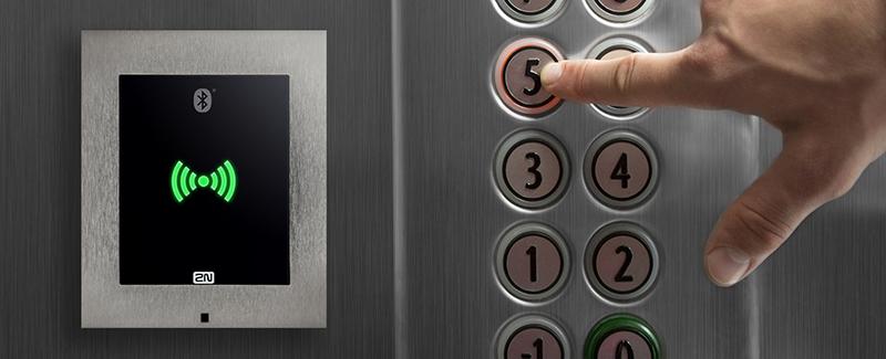 Un lector de tarjeta RFID y una mano pulsando un botón del piso del ascensor.