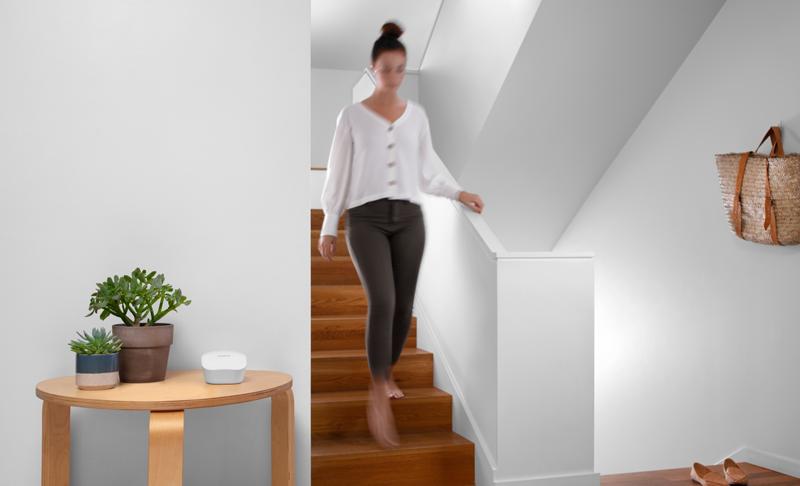 Una mujer bajando las escaleras de su casa y al lado el router eero de Amazon encima de una mesa.