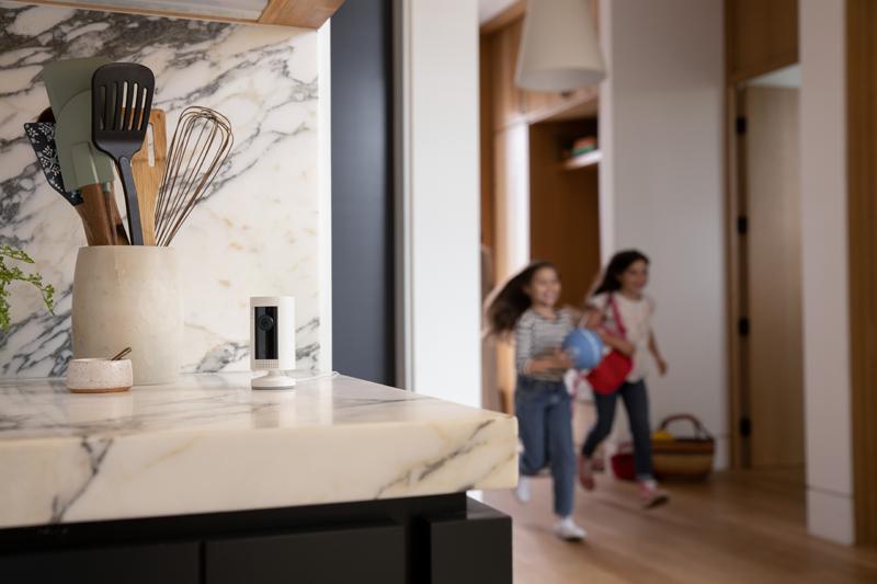 Unas niñas corriendo por el pasillo de una casa y la Ring Indoor Cam puesta en una encimera.