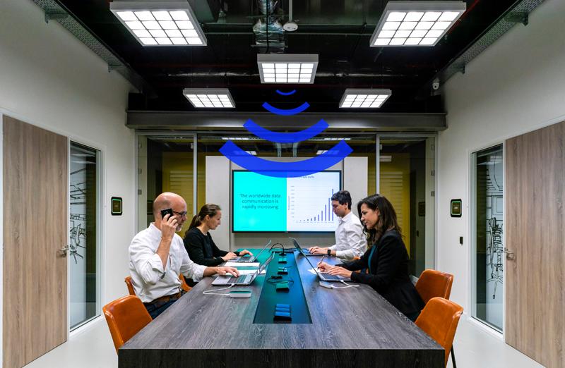 Cuatro personas en una oficina con la conectividad LiFi.