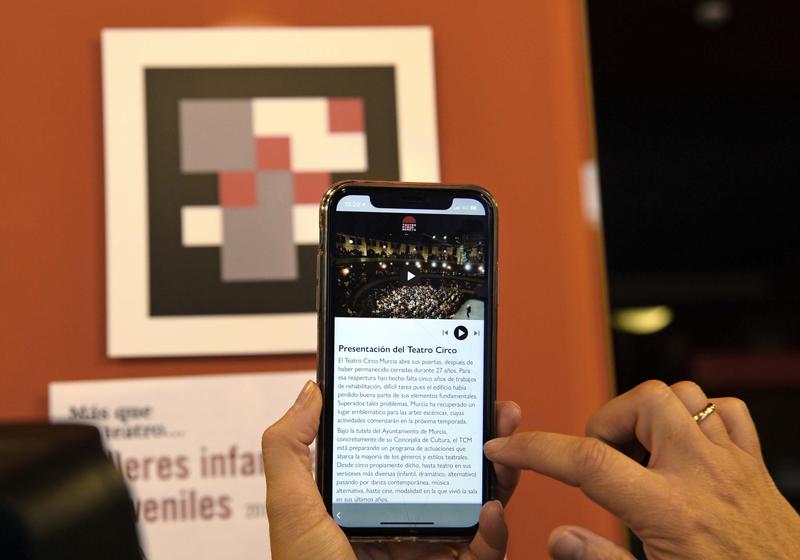 Dos manos con un móvil leyendo un código QR del Teatro Circo de Murcia.