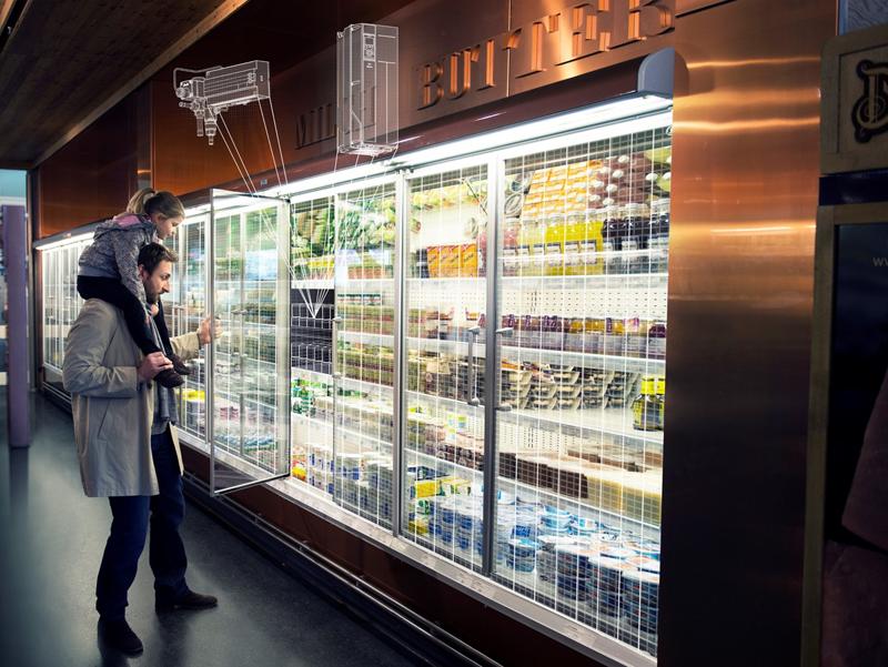 Un hombre y una niña delante de una cámara frigorífica de un comercio.