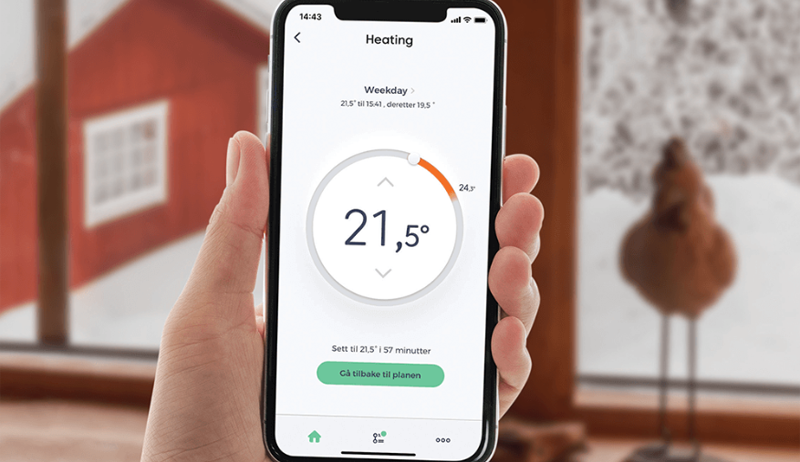 Una mano con un móvil marcando la temperatura interior de un hogar.