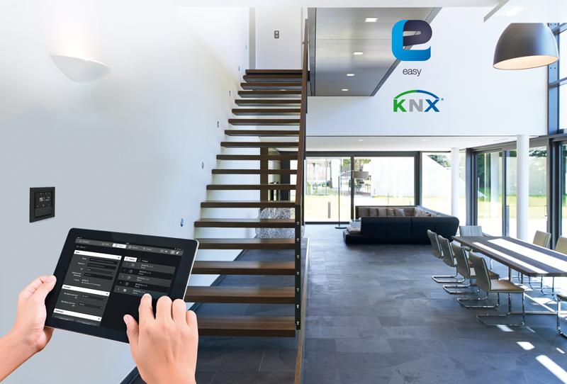 Una persona controlando una tablet para gestionar los dispositivos inteligentes en el interior de una casa.