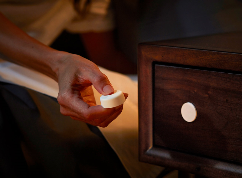 Una mano sujetando el Smart Button Philips Hue de Signify.