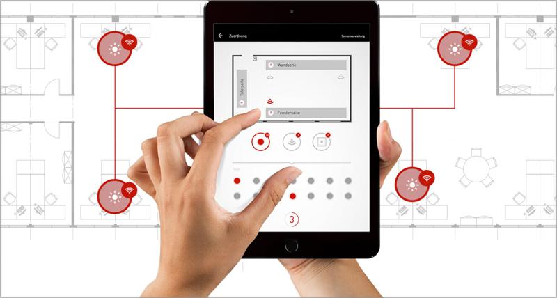 Una mano con una tablet gestionando la iluminación inteligente con la aplicación LiveLink de Trilux.