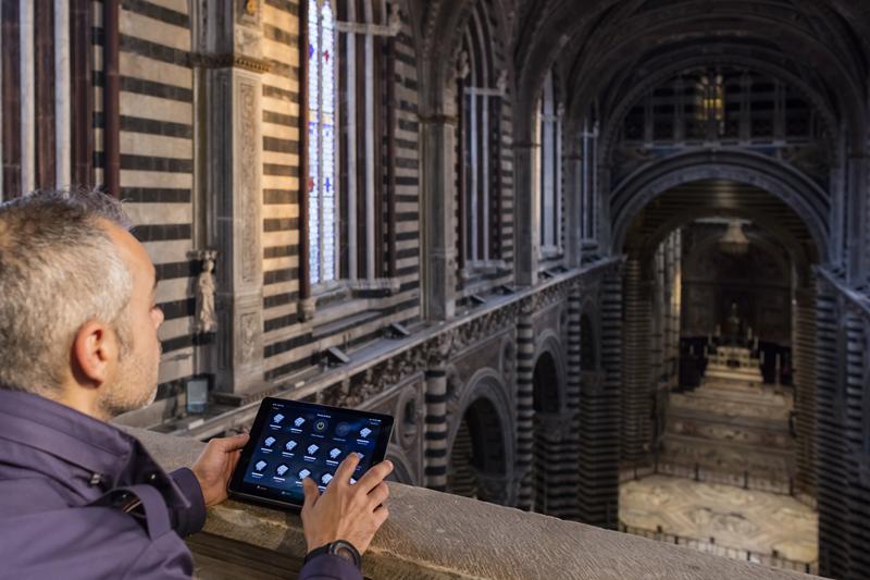 Un operario controlando la iluminación de la Catedral de Siena desde una tablet.