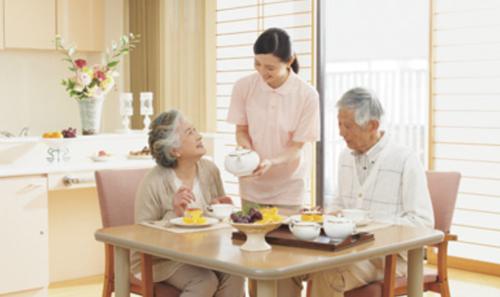 Dos ancianos desayunando mientras les ayuda una enfermera.