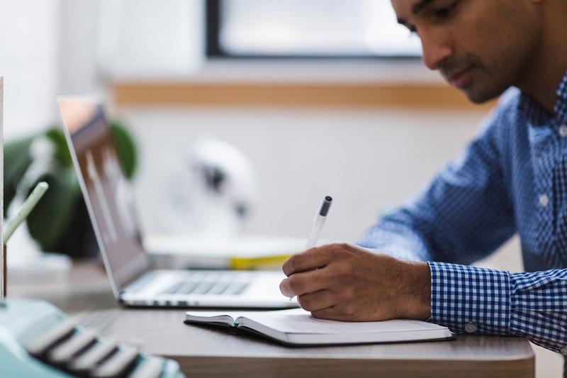 Un hombre estudiando delante de un ordenador.