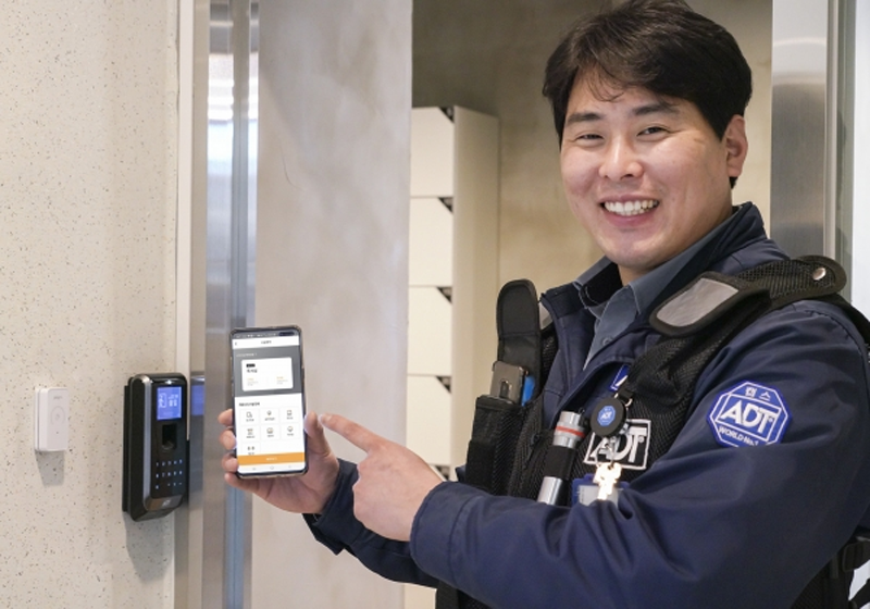 Uno de los empleados de SK Telecom con el móvil al lado de una cerradura inteligente.